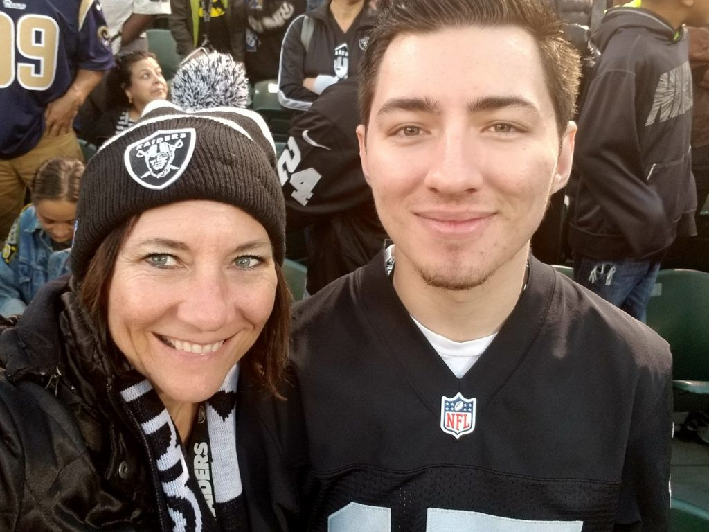 Photo of Christie Fisher in Raiders gear with her son sitting to the right of her in the photo