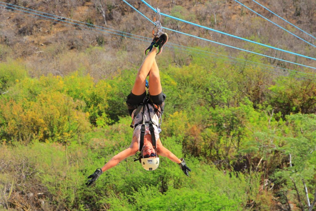 Photo of Christie hanging upside down from a zip line surrounded by greenery in the background