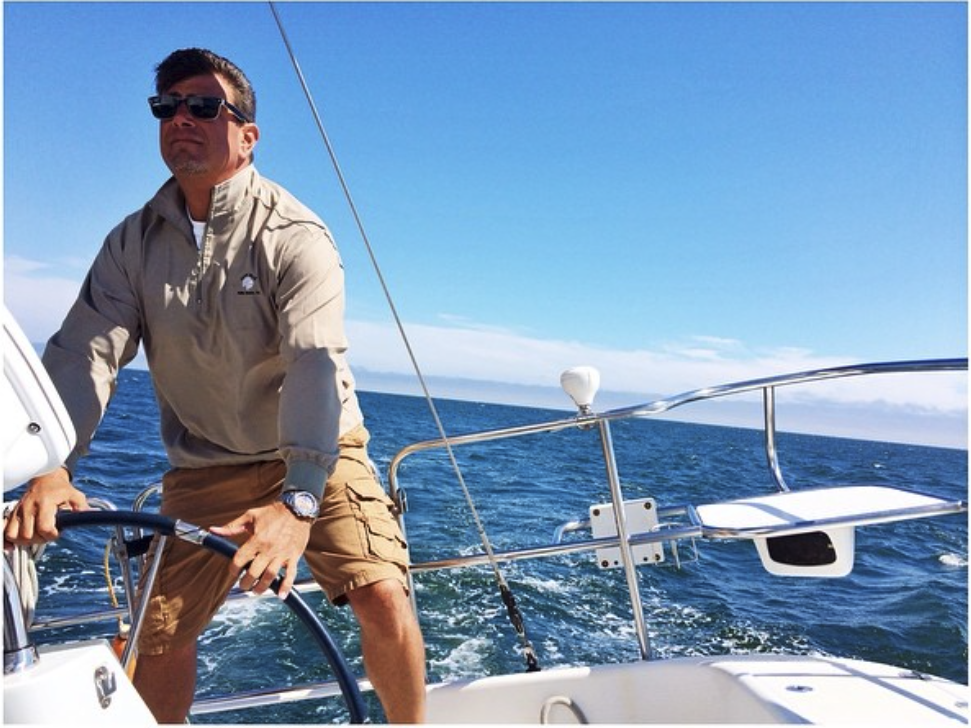 A photo of David Bristow on a sailboat with a blue sky in the background